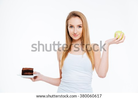 Happy beautiful young woman standing and holding chocolate cake and green apple over white background - stock photo