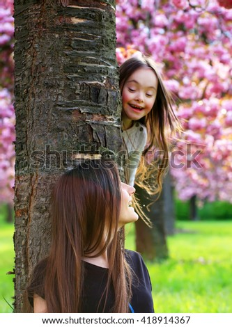 Happy beautiful young woman with girl in blossom park with trees and flowers. - stock photo