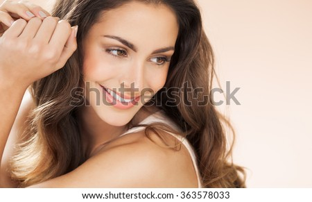 Happy beautiful young woman with long hair smiling over beige background. Fashion and beauty concept in studio.  - stock photo