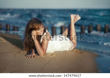 Happy beauty young woman lying on the beach - stock photo