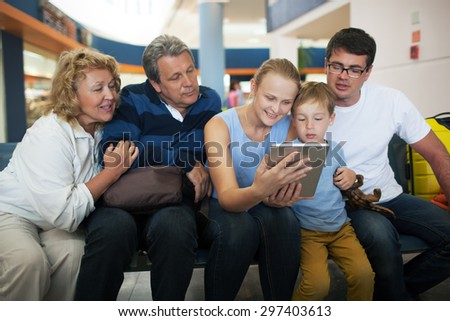 Happy big family at the airport. Child, parents and grandparents  watching something on tablet computer to fill in time while waiting in the lounge - stock photo