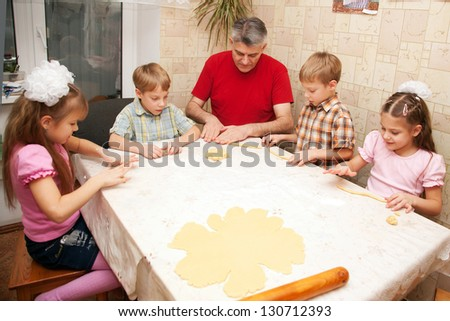 Happy big family cooking a pie together. Father and four children, two boys and two girls playing with dough in the kitchen. - stock photo