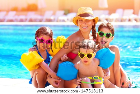 Happy big family having fun at the pool, spending summer vacation together, wearing funny colorful sunglasses, enjoyment and pleasure concept - stock photo