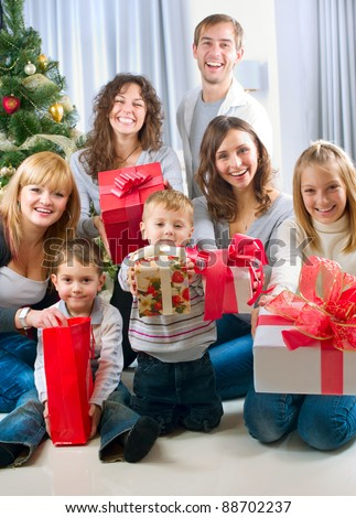 Happy Big family holding Christmas presents at home.Christmas tree - stock photo