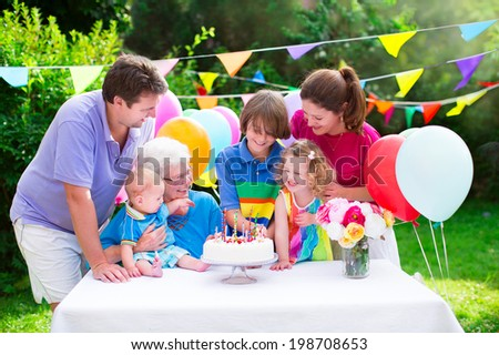 Happy big family - young parents, grandmother, three kids, teenage boy, toddler girl and little baby celebrating birthday party with cake and candles in the garden decorated with balloons and banners - stock photo