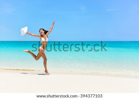 Happy bikini woman jumping of joy and success on perfect white sand beach on caribbean tropical vacation. Holiday girl with sexy slim suntan body running of freedom and happiness.  - stock photo