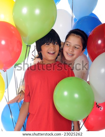 Happy biracial siblings surrounded by helium balloons. - stock photo