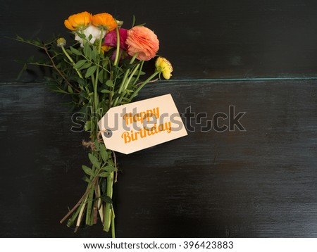 Happy birthday - beautiful bouquet of flowers and a blank textfield with copyspace on a dark wooden background  - stock photo