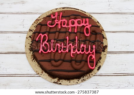 Happy Birthday Cake, A Chocolate Happy Birthday Cake over a distressed wood background - stock photo