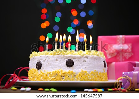 Happy birthday cake and gifts, on black background - stock photo