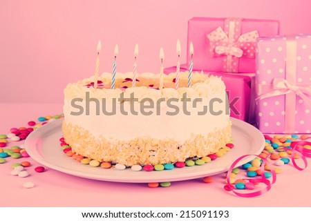 Happy birthday cake and gifts, on pink background - stock photo