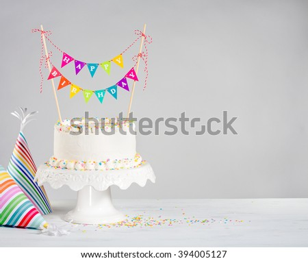 Happy Birthday cake and party hats - stock photo