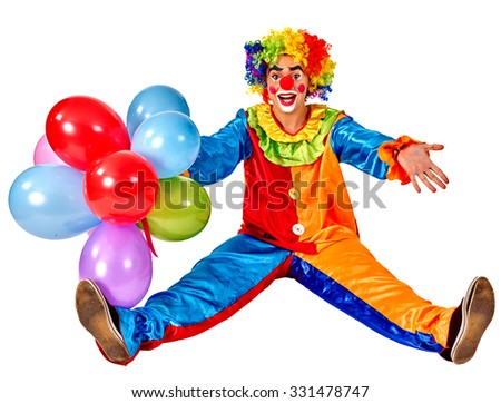 Happy birthday clown holding a bunch of balloons and sitting on floor.  Isolated. - stock photo