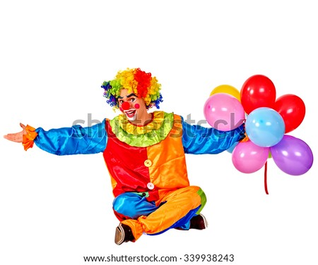 Happy birthday clown holding a bunch of balloons sitting on floor.  Isolated. - stock photo