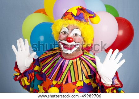 Happy birthday clown with balloons, holding his hands in a surprised gesture. - stock photo