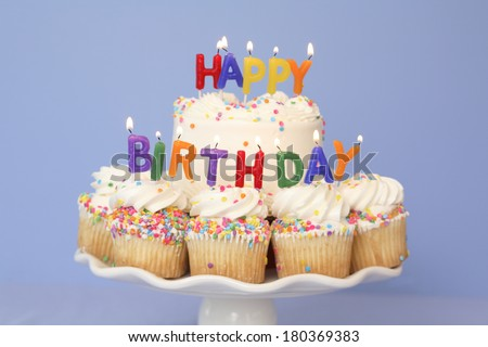 Happy Birthday lit candles cupcakes and cake on stand with blue background - stock photo