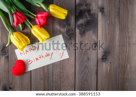 Happy birthday message and tulips flower on table - stock photo