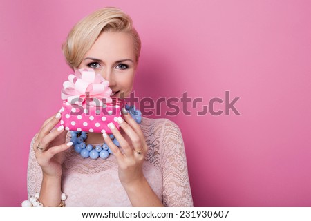 Happy birthday. Sweet blonde woman holding small gift box with ribbon. Soft colors. Studio portrait over pink background - stock photo