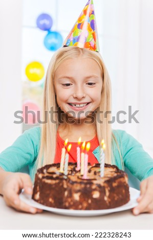 Happy birthday to me! Happy little girl looking at the birthday cake and smiling - stock photo