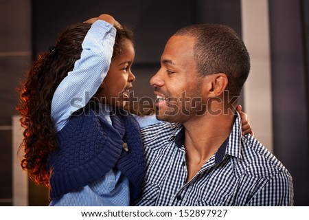 Happy black father and cute little daughter embracing, smiling. - stock photo