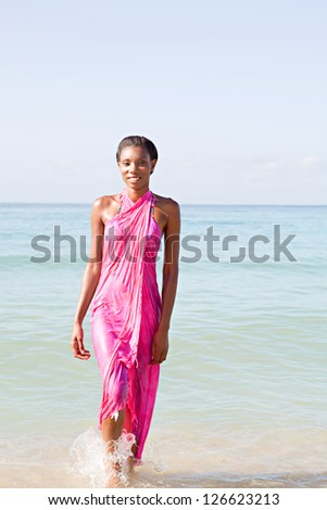 Happy black woman on a beach, walking out of the sea wearing a bright pink sarong around her body while on vacations. - stock photo