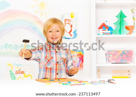 Happy blond boy with hammer and blocks in class - stock photo