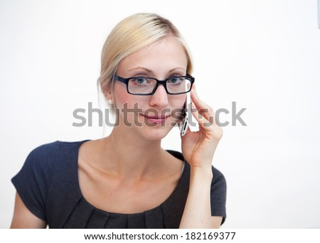 Happy blond businesswoman talking on phone against white background - stock photo
