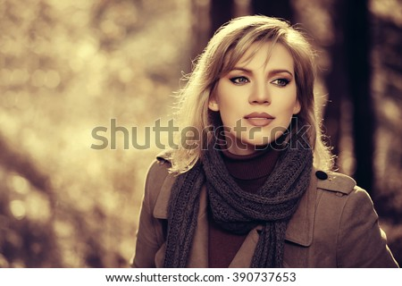 Happy blond fashion woman in classic coat walking outdoor - stock photo