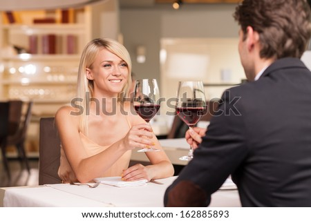 Happy blond girl in love with nice man. Drinking wine in luxury restaurant  - stock photo