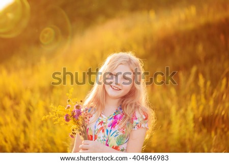 happy blond girl on meadow at sunset - stock photo