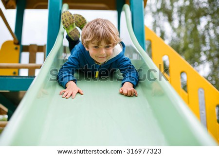 Happy blond kid boy having fun and sliding on outdoor playground. Child smiling. Summer leisure for kids. - stock photo