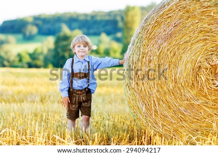 Happy blond kid boy having fun with hay stack on wheat field on warm summer evening. - stock photo