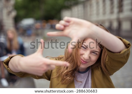 Happy Blond Teen Girl at the Street Showing Framing Hand Gesture While Looking Into Distance. - stock photo