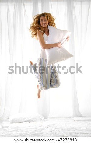 Happy blond woman holding pillow jumping on her bed - stock photo