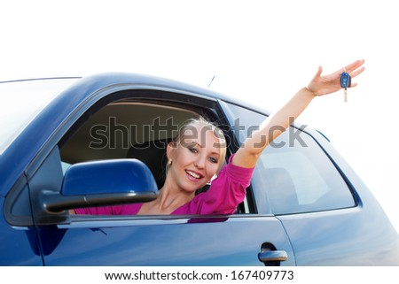 Happy blonde car driver woman showing new car keys in car window - stock photo