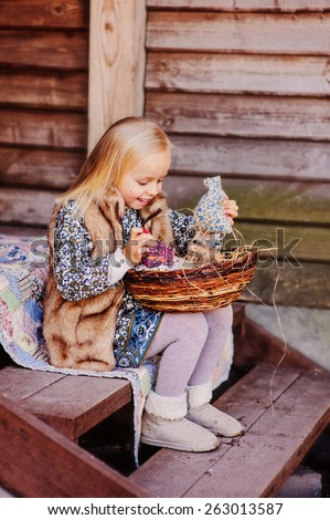 happy blonde child girl playing with easter decorations at country house  - stock photo