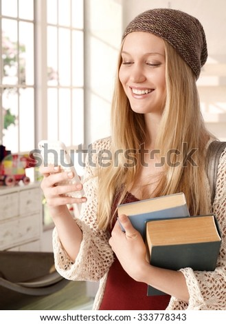 Happy blonde college student holding books, using mobilephone, smiling. - stock photo