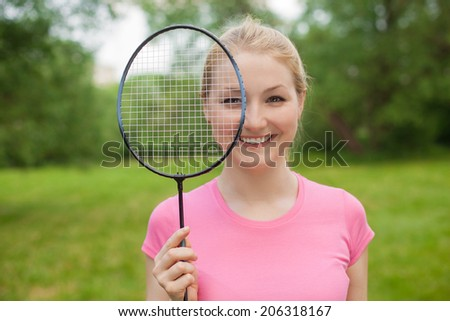 happy blonde girl holding tennis -racket wearing pink t-shirt outdoor in the park  - stock photo