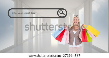 Happy blonde holding shopping bags against bright white hall with windows - stock photo
