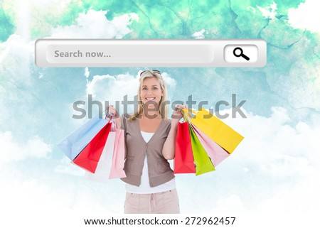 Happy blonde holding shopping bags against green and blue sky - stock photo