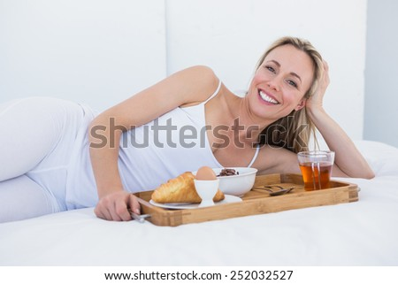 Happy blonde lying and having breakfast in bed at home in the bedroom - stock photo
