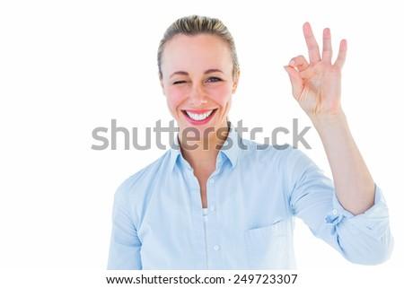 Happy blonde making okay gesture on white bakcground - stock photo