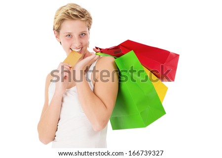 happy blonde shopping woman bites on her golden credit card on white background - stock photo