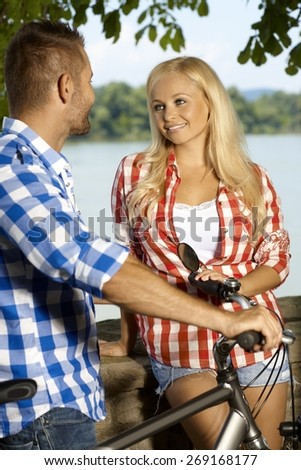 Happy blonde smiling caucasian woman meeting man on bicycle at the riverside outdoor. Looking at each other. - stock photo