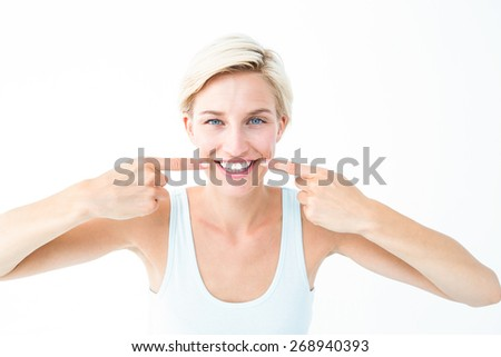 Happy blonde smiling showing her tooth on white background - stock photo