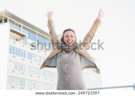 Happy blonde standing and cheering in the city - stock photo