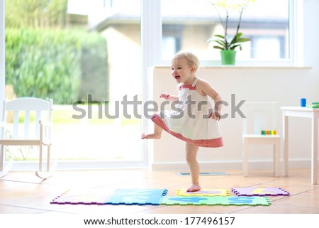 Happy blonde toddler girl having fun dancing indoors in a sunny white room at home or kindergarten - stock photo