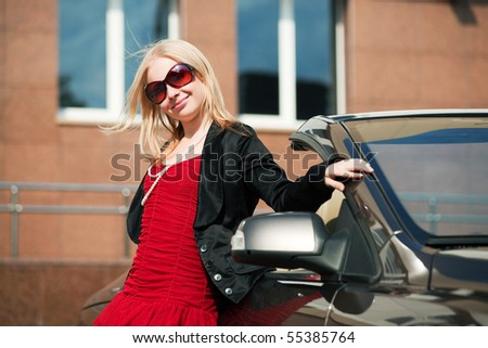 Happy blonde with a convertible car. - stock photo
