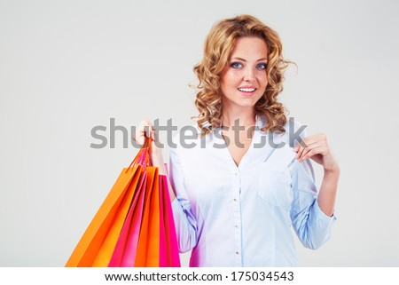 happy blonde woman holding blank card and paper shopping bags, closeup portrait - stock photo