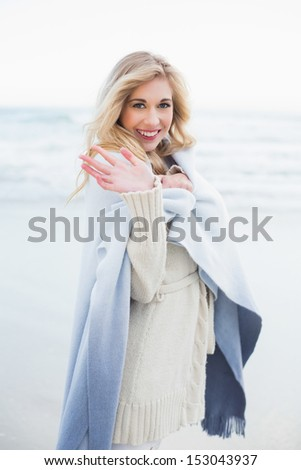 Happy blonde woman in a blanket waving at the camera on the beach - stock photo